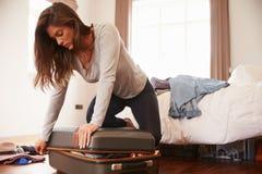 Упаковка женщины на каникулы пробуя закрыть полный чемодан стоковые фотографии rf