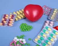 Упаковка таблеток и пилюлек на таблице Красное сердце Стоковые Изображения