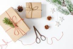Упаковывая подарки рождества в коробках на белом взгляд сверху предпосылки Стоковое Изображение RF