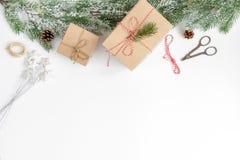 Упаковывая подарки рождества в коробках на белом взгляд сверху предпосылки Стоковые Фотографии RF