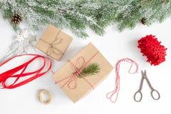 Упаковывая подарки рождества в коробках на белом взгляд сверху предпосылки Стоковая Фотография