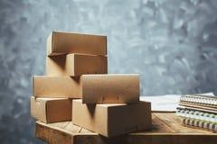 Упакуйте коробку на деревянной таблице стола с предпосылкой бетонной стены стоковая фотография