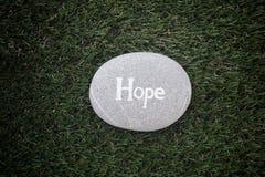 упование Камень при надежда слова лежа на зеленой траве Стоковые Изображения
