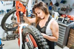 Упорно добиваться женский мастер ремонтируя велосипед горы стоковое изображение rf