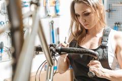 Упорно добиваться женский механик ремонтируя велосипед в гараже стоковое изображение