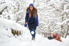 управлять зимой розвальней потехи девушка и мальчик sledding стоковые изображения