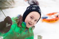 управлять зимой розвальней потехи помощь девушки для того чтобы вытянуть веревочку для того чтобы исправить рождественская елка Стоковые Фотографии RF