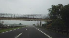Управлять на итальянском шоссе с проливным дождем Управлять съемкой, точка зрения водителя сток-видео