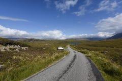 Управляющ на сиротливой дороге через красивую шотландскую вересковую пустошь, Assynt, Шотландия, Великобритания стоковые изображения rf