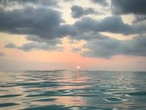 управляет его заходом солнца берега моря персоны kayak к Стоковое Изображение