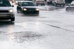 Управлять автомобилей на дороге с водой puddles во время проливного дождя Стоковое Изображение RF