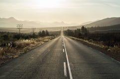 Управлять в заход солнца на шоссе в ландшафте горы стоковые изображения