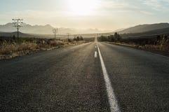 Управлять в заход солнца на шоссе в ландшафте горы стоковые изображения rf