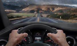 Управлять в ненастной погоде Взгляд от угла водителя пока руки на колесе Лобовое стекло брызнутое дождем Стоковое Изображение RF