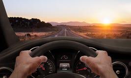 управлять заходом солнца Взгляд от угла водителя пока руки на колесе стоковое фото