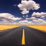 Управлять на дороге асфальта на симпатичном солнечном дне Стоковое Изображение