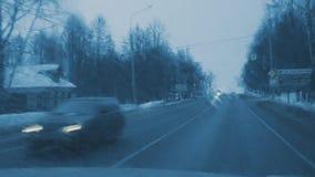 Управлять на дороге зимы вечера Осмотрите через лобовое стекло водителей