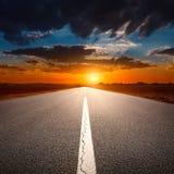 Управлять на пустой дороге асфальта на заходе солнца Стоковые Изображения
