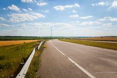 Управлять на пустой дороге асфальта через аграрные поля к заходящему солнцу стоковая фотография