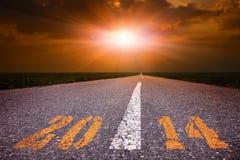 Управлять на пустой дороге к заходящему солнцу 2014 стоковое фото rf