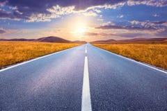 Управлять на пустой дороге к заходящему солнцу Стоковая Фотография