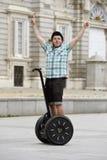 Управлять путешествия города катания headgear шлема безопасности молодого счастливого туристского человека нося segway счастливый Стоковые Изображения