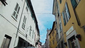 Управлять узкой улицей между красивыми buldings в Gavi, Италия акции видеоматериалы