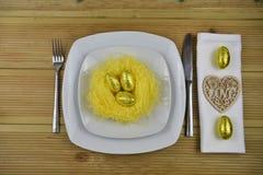 Урегулирование места таблицы пасхи в белизне с handmade желтым гнездом и сияющим золотым цветом eggs с деревянным украшением серд Стоковое Фото