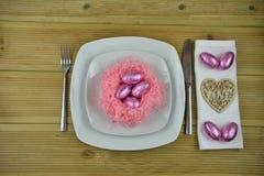 Урегулирование места таблицы пасхи в белизне с handmade розовым гнездом и сияющими яичками шоколада с деревянным украшением сердц Стоковые Изображения RF