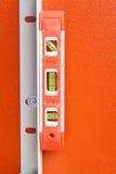 Уровень воды конструкции на оранжевой стене Стоковое фото RF