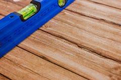 Уровень здания предпосылки голубой на деревянной предпосылке Стоковое Фото