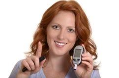 Уровень сахара в крови довольно рыжеволосой женщины контролируя стоковое фото rf