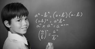 Уровнения математики сочинительства мальчика на классн классном Стоковое фото RF
