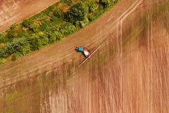 Урожаи трактора распыляя в поле, виде с воздуха стоковое фото rf