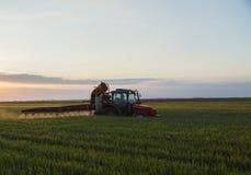 Урожаи трактора распыляя на заходе солнца стоковые фото