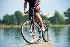Урожай велосипедиста представляя рядом с его велосипедом Стоковое фото RF