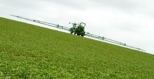 Урожай распыляя в поле стоковые фотографии rf