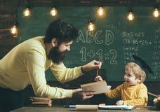 Урок английской грамматики Мальчик учит английскую грамматику в классе Отец учит английской грамматике к сыну английско стоковое фото