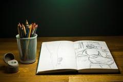 Урок чертежа Sketchbook на таблице с crayons и покрашенными карандашами Стоковое фото RF