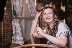 Уродская женщина в национальном платье представляя в деревенском интерьере Стоковое фото RF