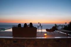 Усаженные девушки на палубе бассейна смотря море Pomos как солнце устанавливают Стоковые Фотографии RF
