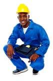 Усаженный африканский работник представляя с усмешкой стоковое фото rf