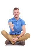 Усаженный молодой вскользь человек предлагает рукопожатие Стоковое фото RF