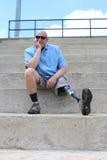 Усаженный человек человека с ампутированной конечностью при простетическая протягиванная нога стоковое изображение