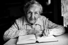 Усаживание бабушки прочитало книги на таблице Пенсионер, Стоковые Изображения