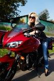 усаживание белокурого мотоцикла девушки красное стоковое изображение