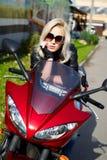 усаживание белокурого мотоцикла девушки красное стоковые фото