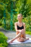 Усаживание девушки, ослабляя в парке, после работать йоги На wa Стоковые Фото
