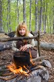 усаживание девушки пущи костра близкое Стоковое Изображение RF