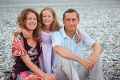 усаживание девушки семьи пляжа счастливое каменистое стоковые изображения